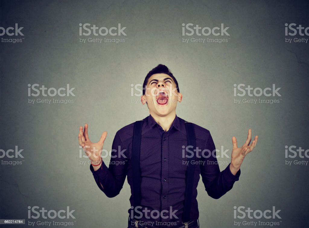 Frustrated desperate young man screaming stock photo