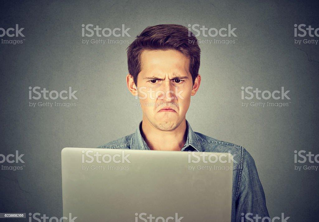 Frustrated disgusted man looking at laptop displeased with email stock photo