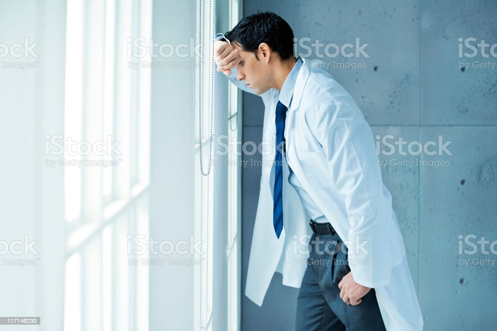 Frustrated doctor leaning on window royalty-free stock photo
