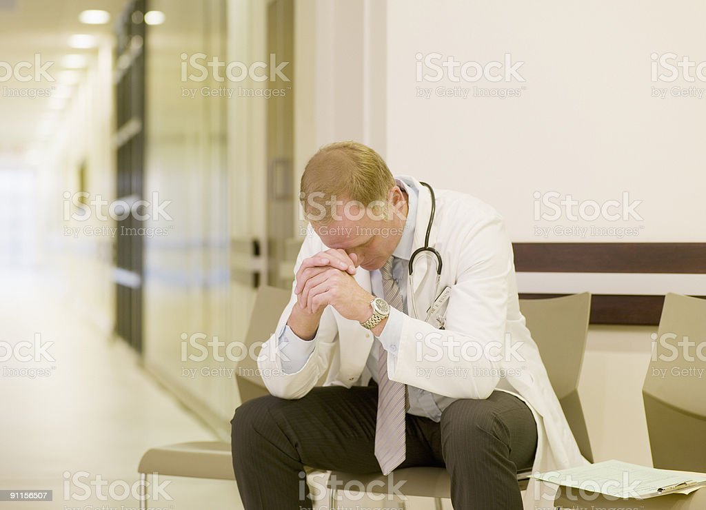 Frustrated doctor sitting in hospital waiting area royalty-free stock photo