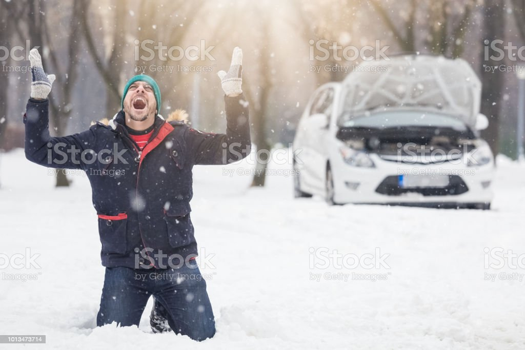 Frustrated driver next to broken car. Winter season road trip problems and assistance concept. stock photo