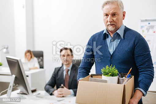 istock Frustrated elderly employee leaving office with box full of belongings 655913700