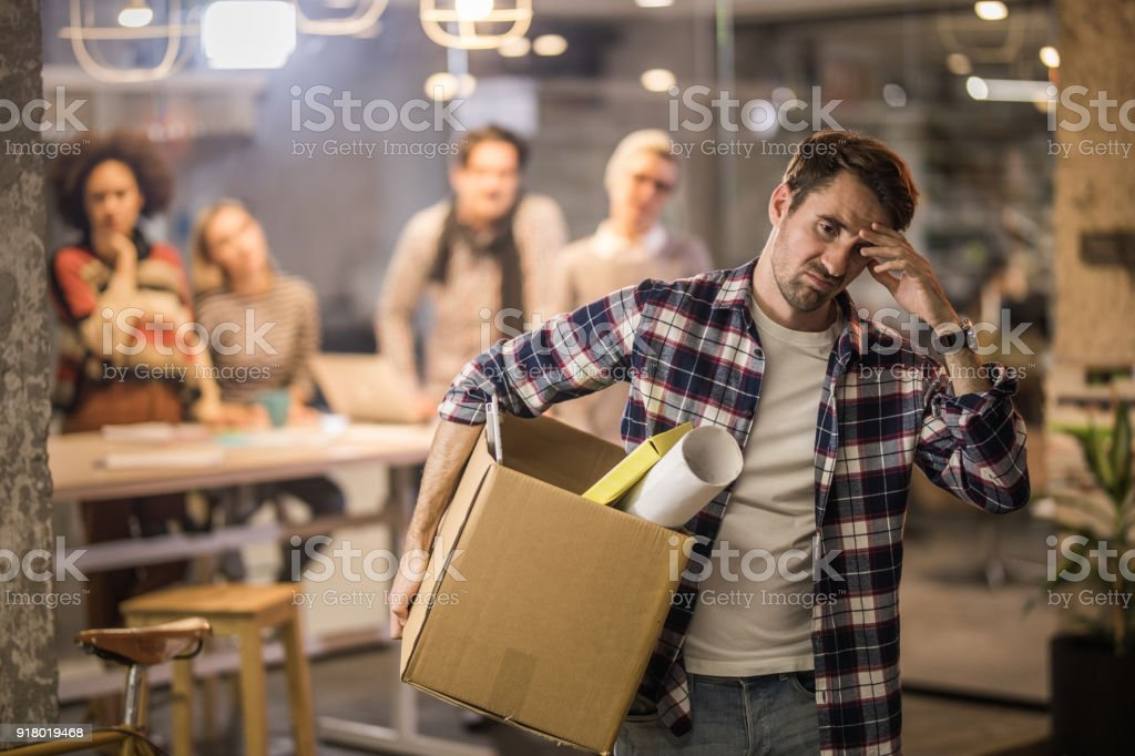 Frustrated entrepreneur leaving the office after being fired. stock photo