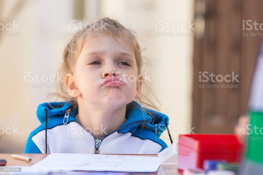 Frustrated girl sitting at a table in courtyard of house stock photo