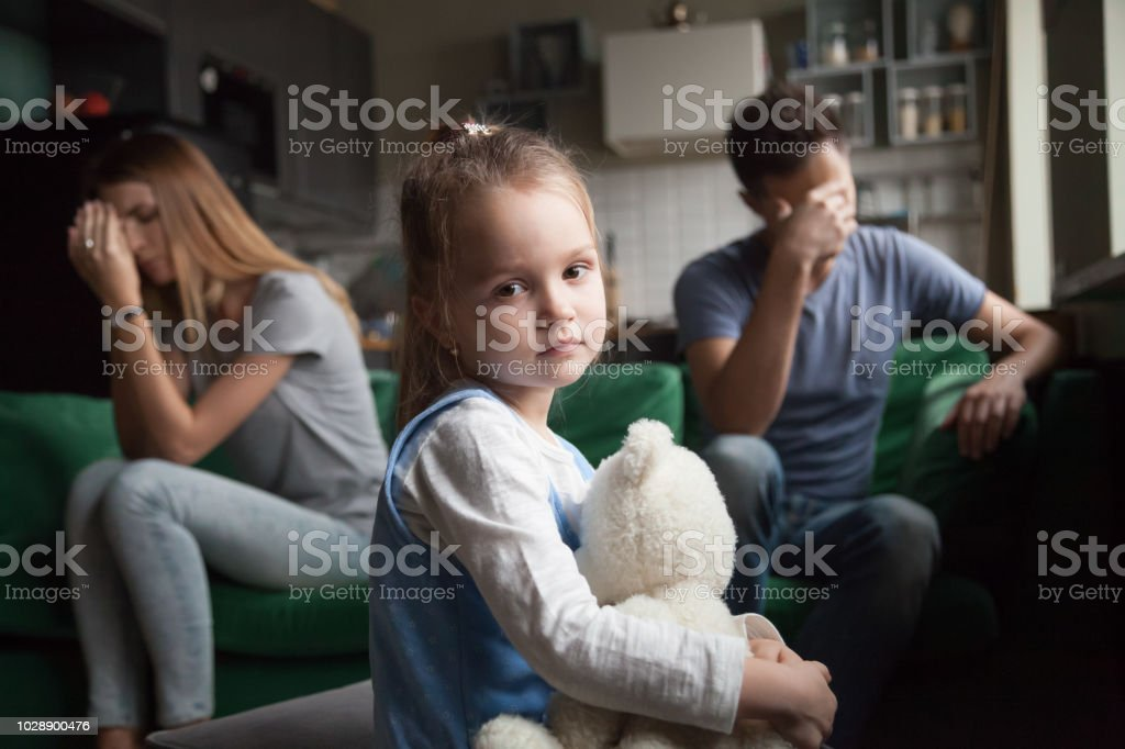 Frustrated girl tired of parents fights, child and divorce concept stock photo