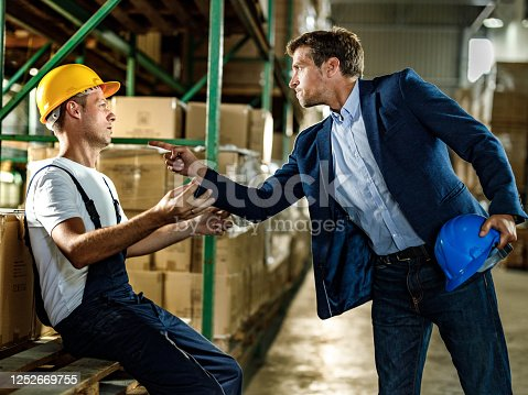 1001622522 istock photo Frustrated inspector threatening his worker in distribution warehouse. 1252669755