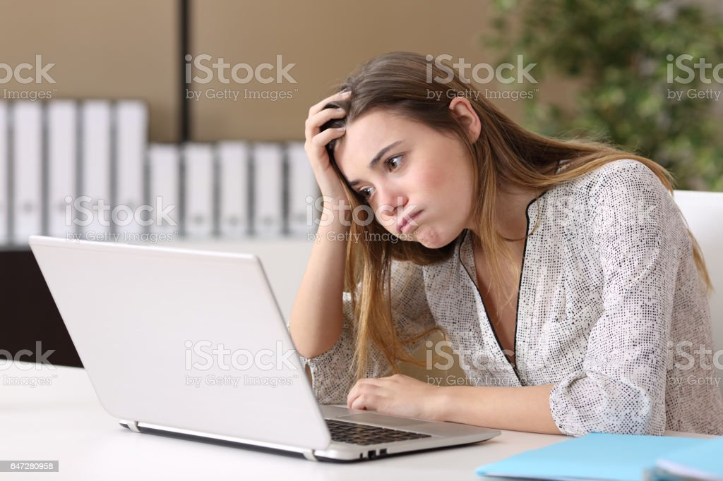 Frustrated intern working on line at office stock photo