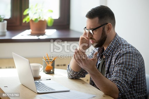 857213750istockphoto Frustrated male employee discussing contract details over the phone. 857213750