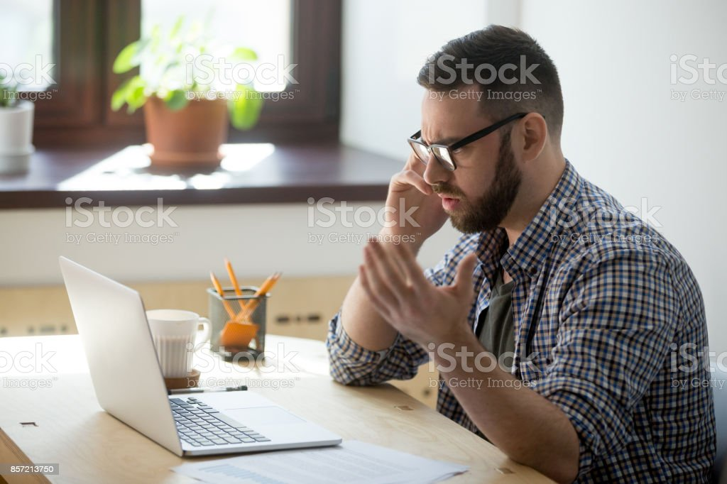 Frustrated male employee discussing contract details over the phone. stock photo