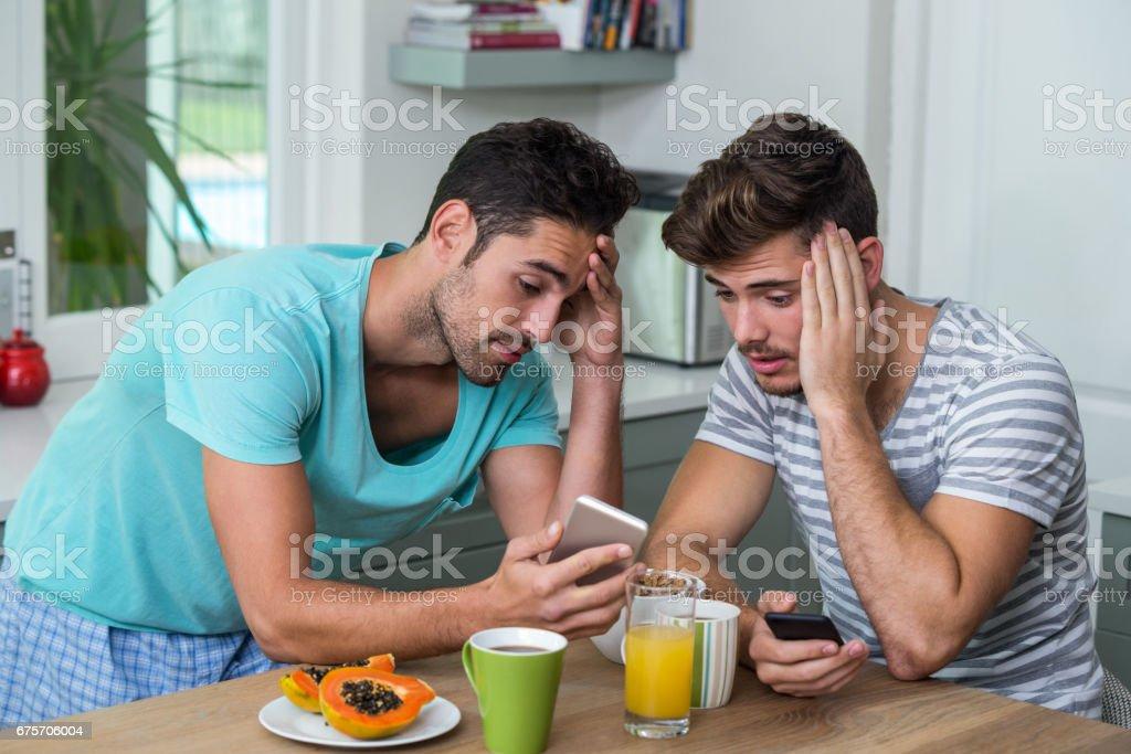 沮喪的男性朋友使用電話 免版稅 stock photo
