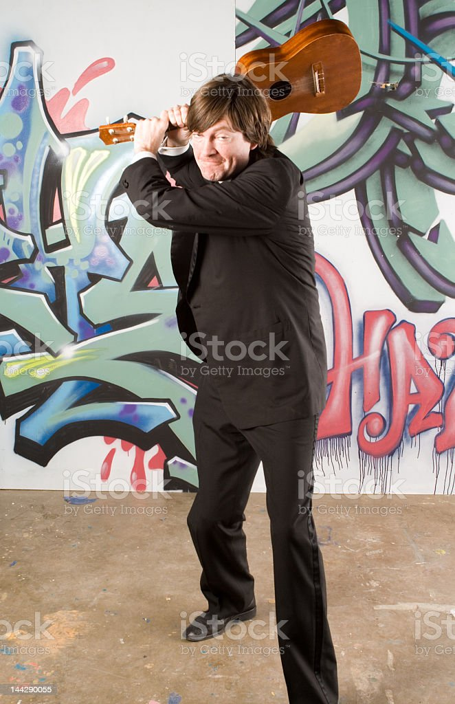 Frustrated Man About to Smash a Ukulele on Cement Floor stock photo