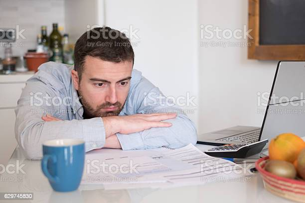 Frustrated man calculating bills and tax  expenses Frustrated man calculating bills and tax  expenses Adult Stock Photo