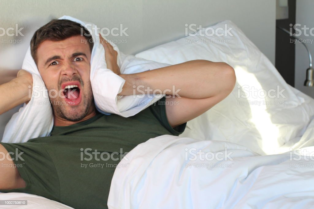 Frustrated man covering his ears with pillow stock photo