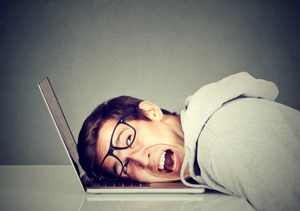Hombre frustrado sintiéndose estresado con su computadora portátil - foto de stock