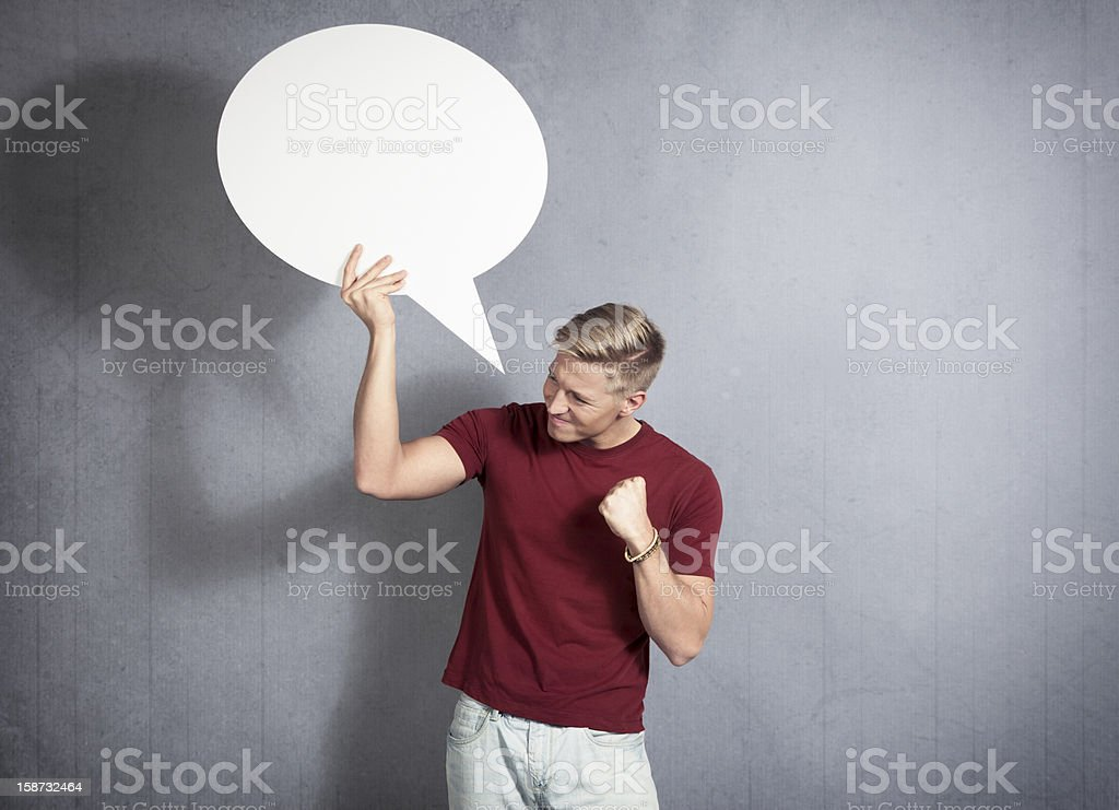 Frustrated man holding white blank speech bubble. royalty-free stock photo