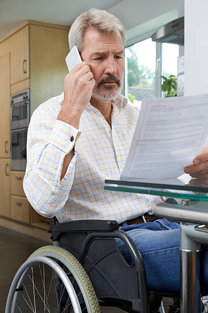 frustrated man in wheelchair making phone call whilst reading le - social security check stock photos and pictures