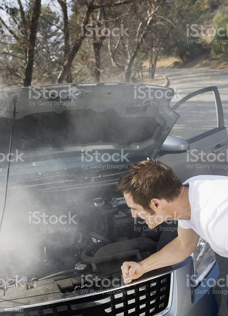Frustrated man looking at smoking car engine royalty-free stock photo