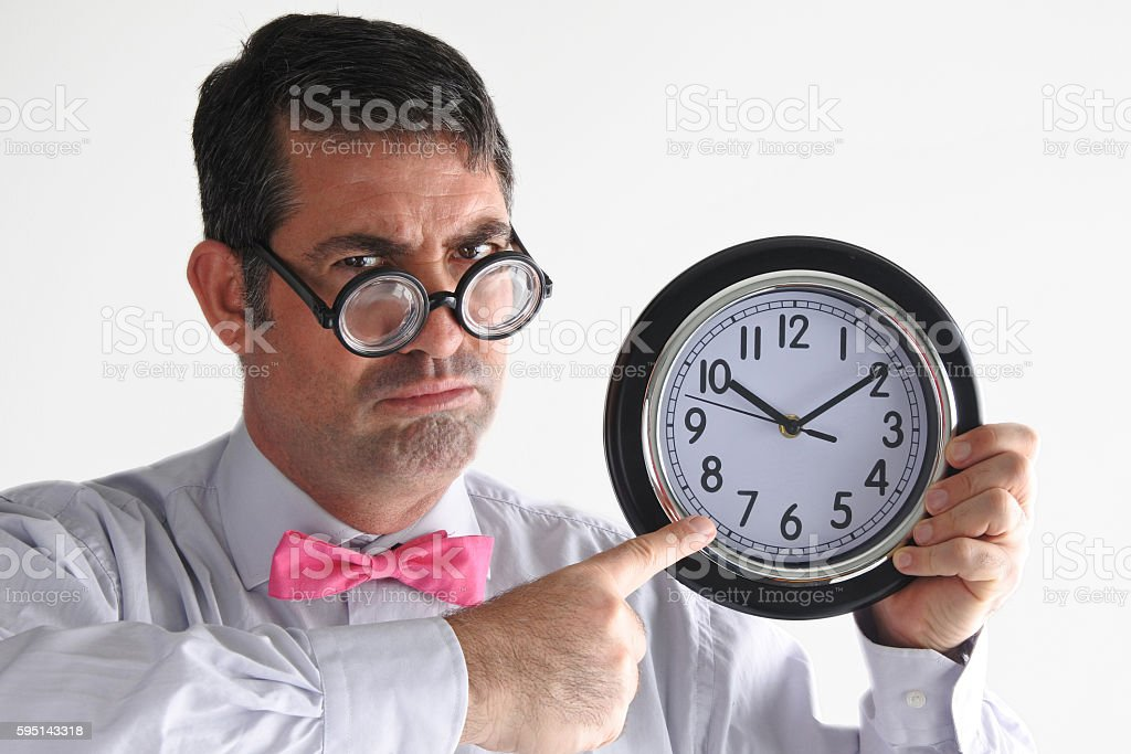Frustrated man manager points to the time on a clock stock photo
