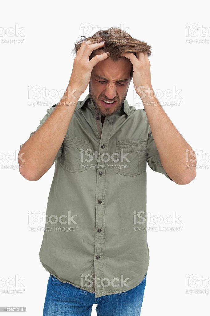 Frustrated man pulling his hair and looking down stock photo