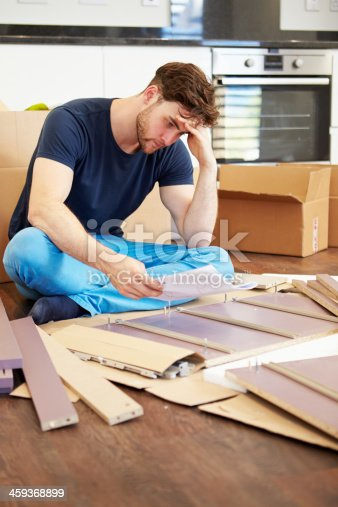 459373065 istock photo Frustrated Man Putting Together Self Assembly Furniture 459368899