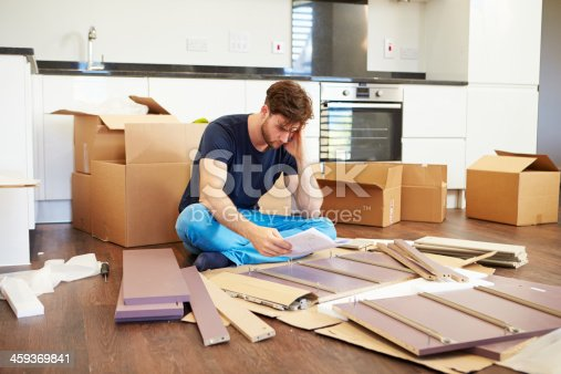 459373065 istock photo Frustrated Man Putting Together Self Assembly Furniture 459369841