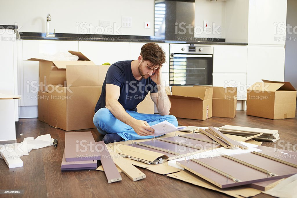 Frustrated Man Putting Together Self Assembly Furniture stock photo