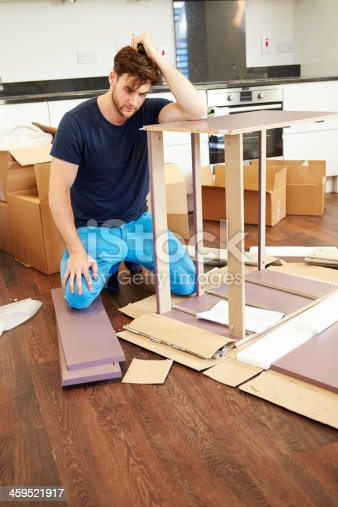 459373065 istock photo Frustrated Man Putting Together Self Assembly Furniture 459521917