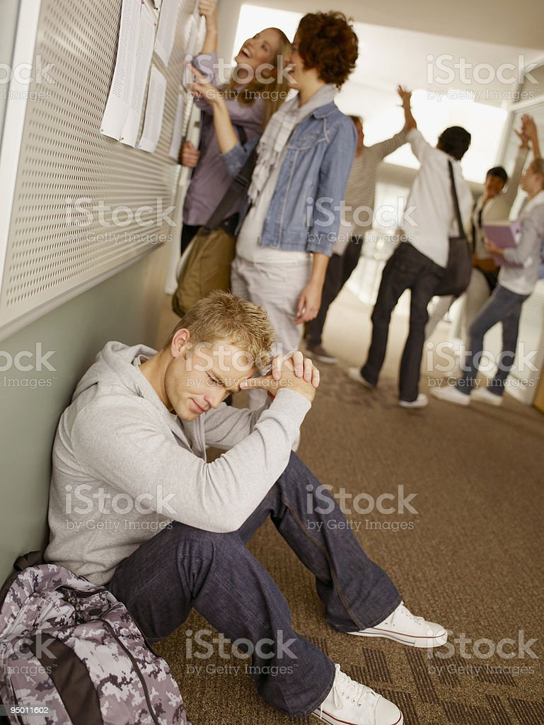 Frustrated man sitting near college students checking test scores in corridor stock photo