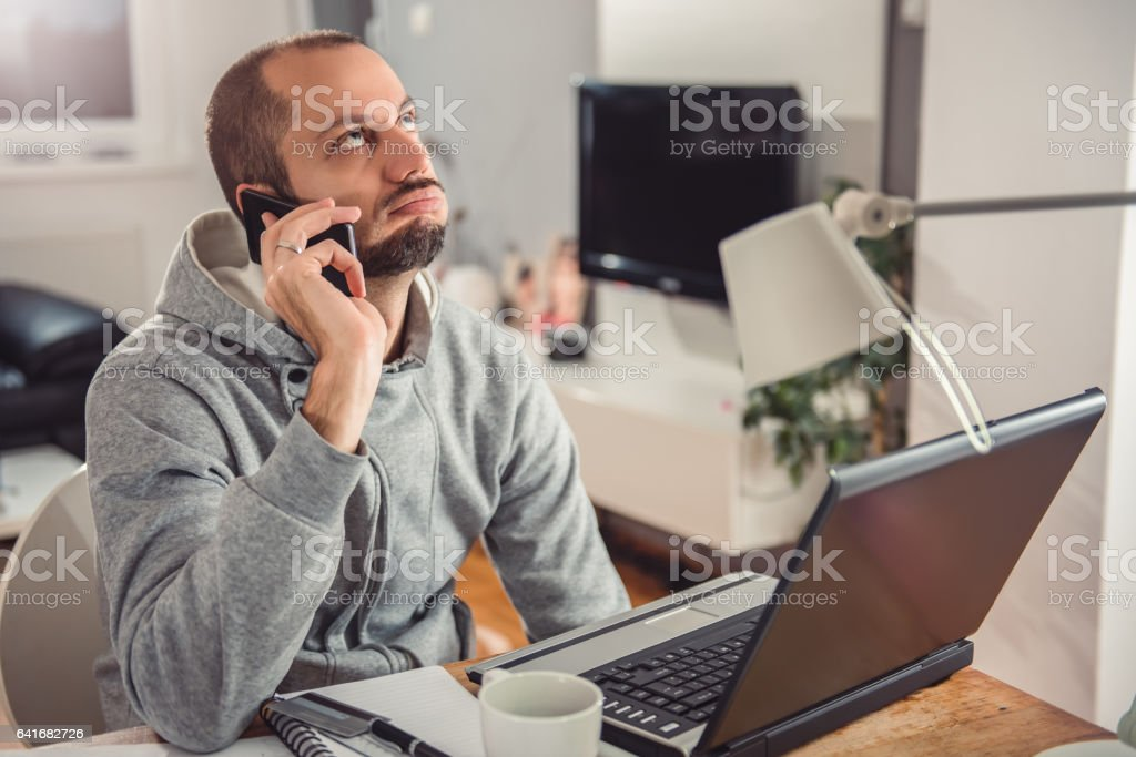 Frustrated man talking on smart phone stock photo
