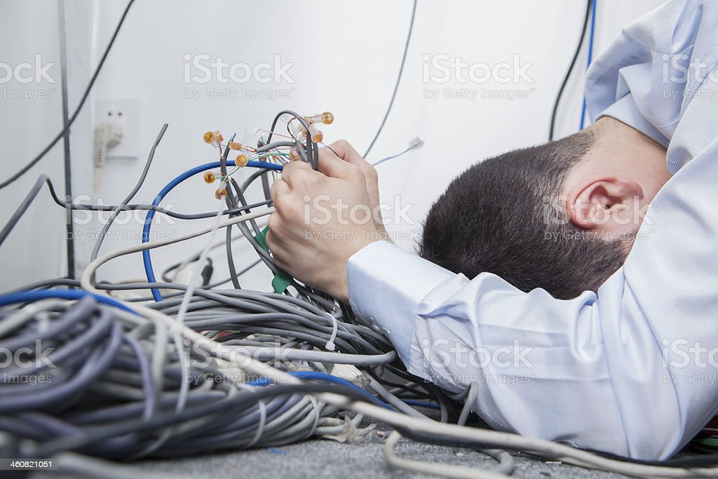 Frustrated man trying to figure out computer cables stock photo