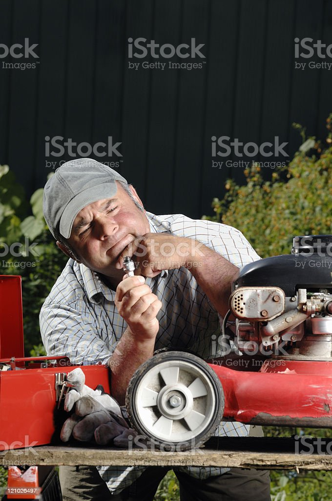 Frustrated man trying to fix his old lawnmower stock photo