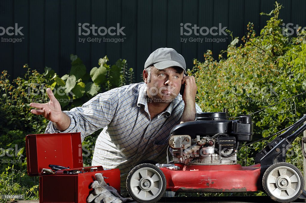 Frustrated man trying to fixing a lawnmower on the phone stock photo