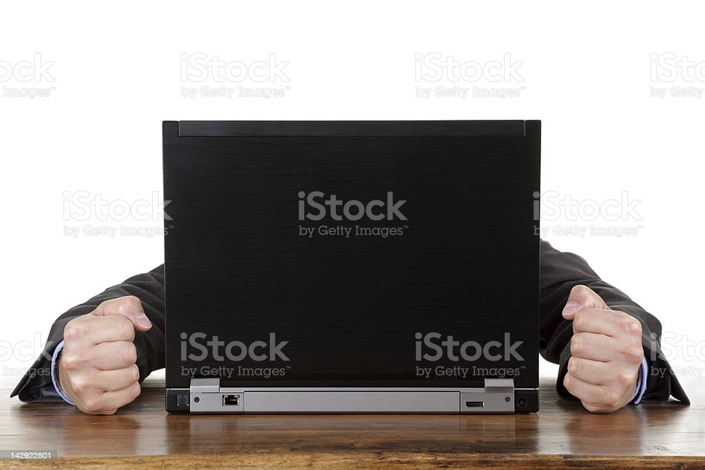 Frustrated man with balled fists at a computer royalty-free stock photo