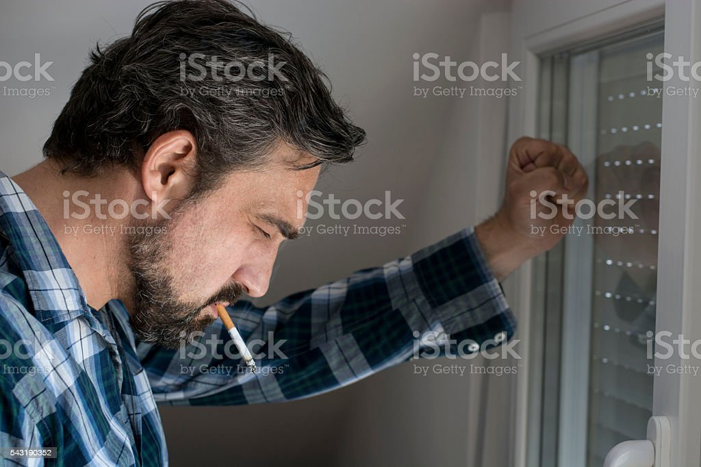 Frustrated man with cigarette stock photo