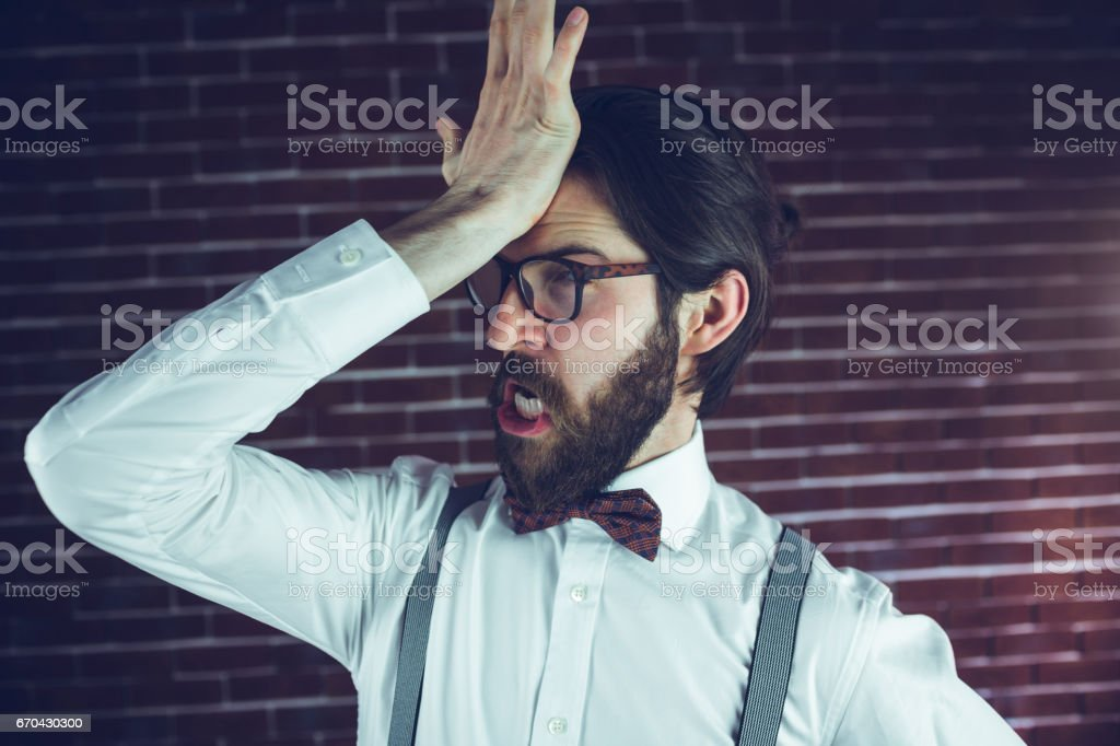 Frustrated man with head in hand stock photo