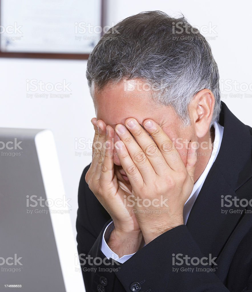 frustrated mature businessman with hands on his face royalty-free stock photo