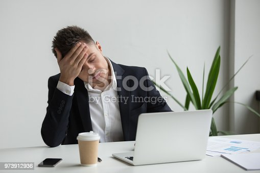 istock Frustrated millennial businessman having strong headache tired from laptop work 973912936