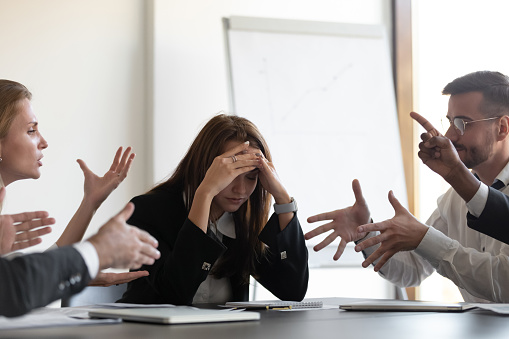 Frustrated millennial female worker sitting at table with colleagues, felling tired of working quarreling at business meeting. Upset stressed young businesswoman suffering from head ache at office.