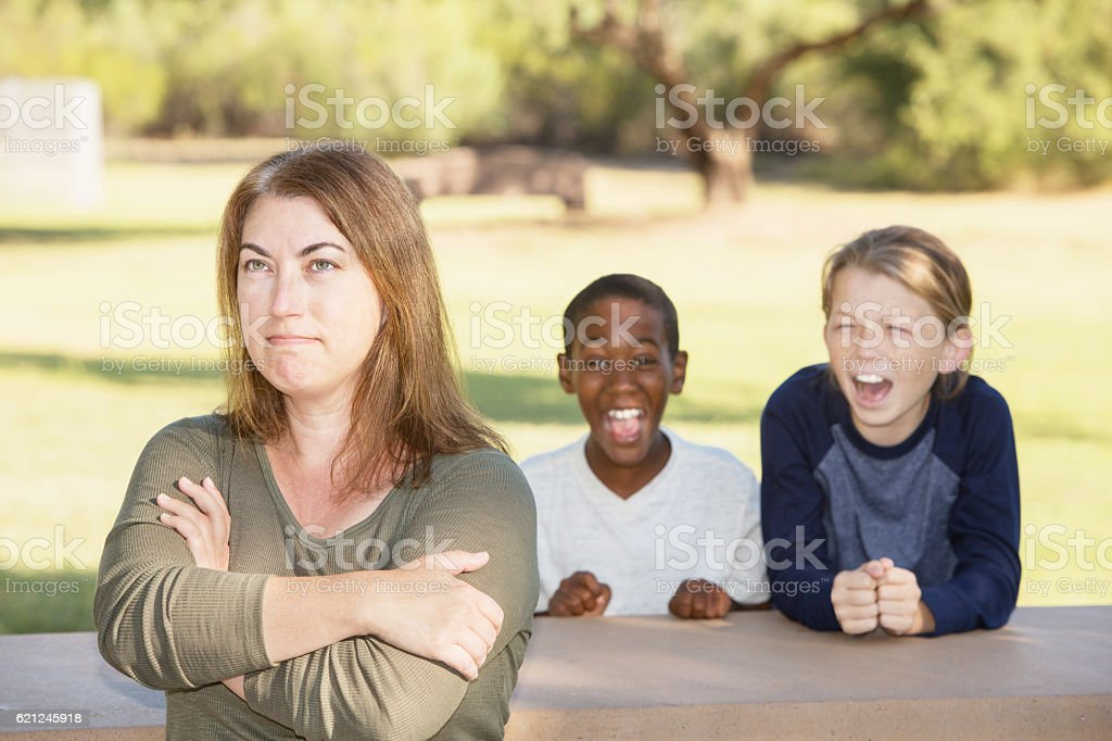 Frustrated mother with children at park stock photo