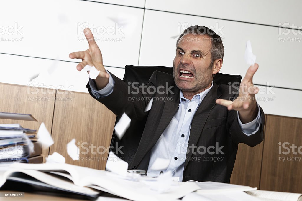 Frustrated office manager tearing document. stock photo