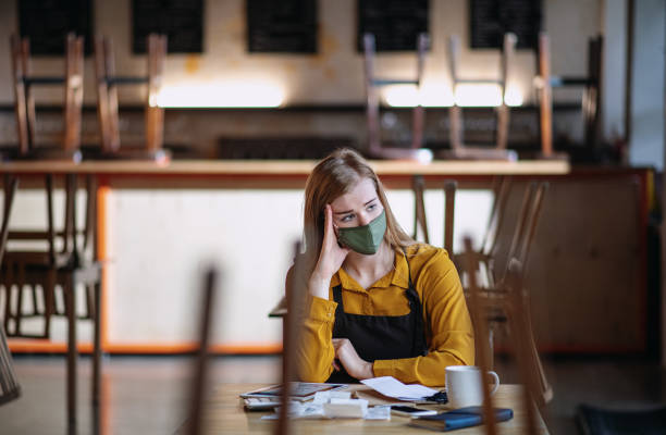 Frustrated owner sitting at table in closed cafe, small business lockdown due to coronavirus. stock photo
