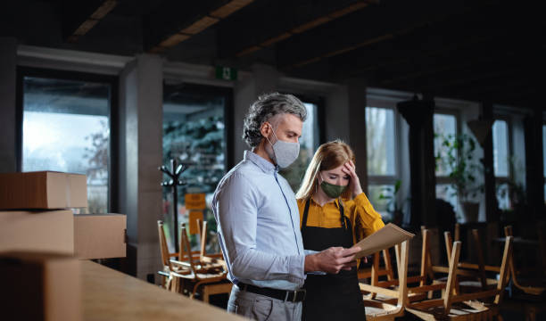 Frustrated owner with waitress in closed cafe, small business lockdown due to coronavirus. stock photo