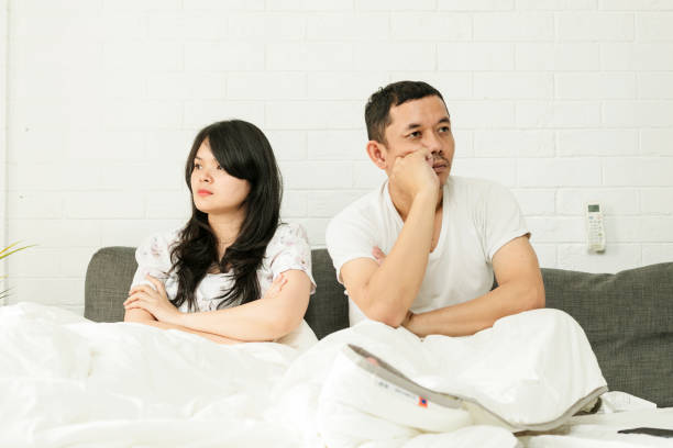 Frustrated sad a husband sit on bed think of relationship problems stock photo