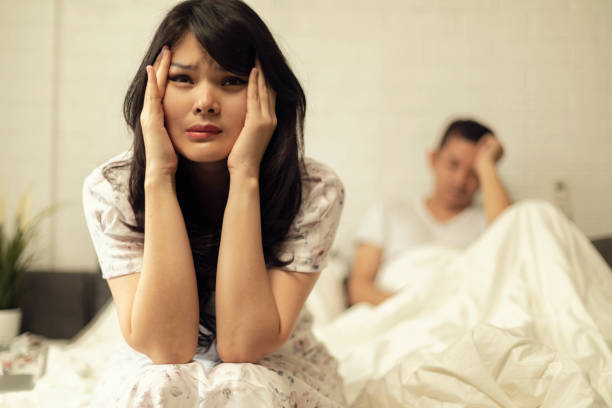 Frustrated sad a wife sit on bed think of relationship problems an asian woman frustrated on the bed think of troubled relationship asian love triangle stock pictures, royalty-free photos & images