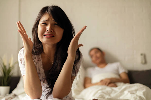 Frustrated sad a wife sit on bed think of relationship problems stock photo