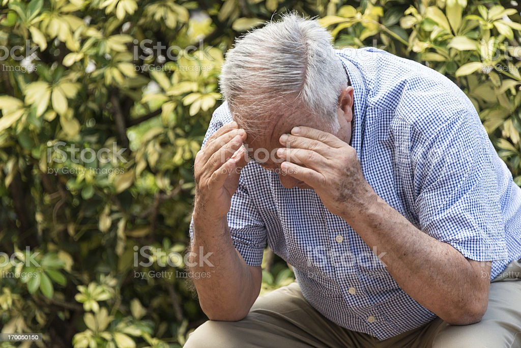 Frustrated senior man with head in his hands stock photo