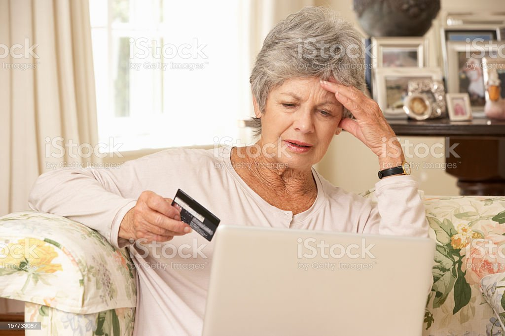 Frustrated Senior Woman Sitting At Home Using Laptop stock photo