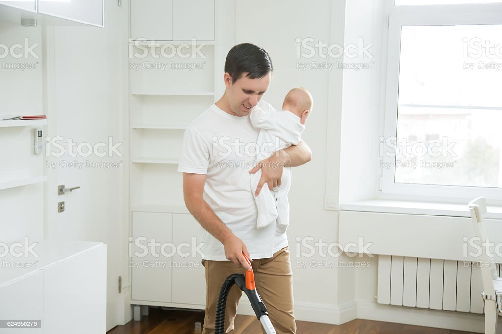 Frustrated stay-at-home dad vacuum cleaning the carpet holding a - foto de stock