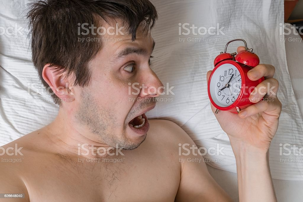 Frustrated, stressed man is waking up looking at alarm clock. - foto de acervo
