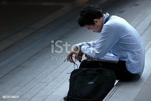 istock Frustrated stressed young Asian business man feeling strain or tried or disappointed at staircase. 902516620